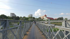 People walking on a bridge over Somesul Mic River in Cluj-Napoca Stock Footage