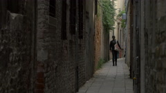 Four people walking on a narrow street in Venice - stock footage