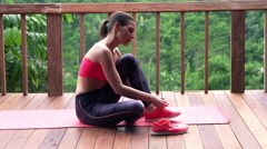 Sporty woman putting on shoes and doing laces on terrace, super slow motion 120f Stock Footage