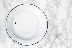Back Side of Empty White Vintage Enamel Plates on Marble - stock photo