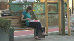 Woman sitting on a bench next to a dumpster, Cluj-Napoca - stock footage