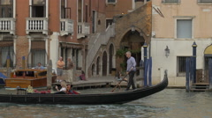 Gondolier paddling a gondola with two tourists in Venice Stock Footage