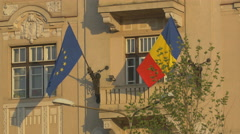 European Union flag and Romanian flag waving on a building, Cluj-Napoca Stock Footage