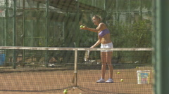 Woman playing tennis on a tennis field in Iulius Park in Cluj-Napoca Stock Footage