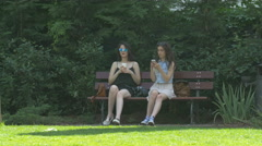 Young women sitting on a bench in Iulius Park in Cluj-Napoca Stock Footage