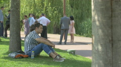 Man sitting on grass in Iulius Park in Cluj-Napoca Stock Footage