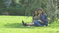 Young women lying on grass in Iulius Park in Cluj-Napoca Stock Footage