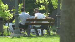 Young men sitting on a bench in Iulius Park in Cluj-Napoca Stock Footage