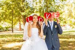 wedding couple holding hands in the word love - stock photo