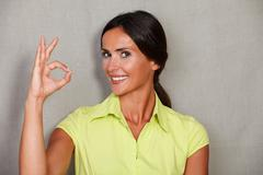 Satisfied woman showing ok sign and smiling satisfied while looking at camera Stock Photos