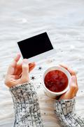 Stock Photo of Woman holds a cup of tea and photo. Winter fabric background wit