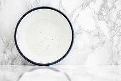 Empty White Vintage Enamel Plate on Marble - stock photo