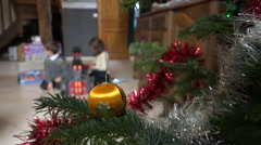 Kids playing with new toys close to christmas tree (baulbe & tinsel) slow motion - stock footage