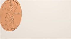 A penny tumbles onto a white surface. - stock footage