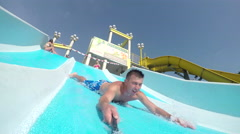 SELFIE: Smiling man sliding down super fast water slide Stock Footage