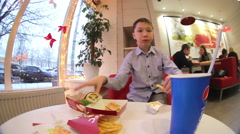 Boy eating a hamburger and fries at the cafe. Stock Footage
