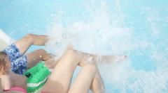 SLOW MOTION CLOSEUP: Family sitting on pool edge splashing water Stock Footage