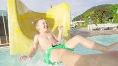 SLOW MOTION: Happy kid smiling sliding down the toboggan in aquapark Stock Footage