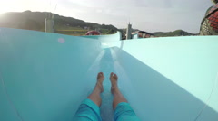 FPV: Man sliding down fun water slide at summer sunset Stock Footage