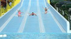 SLOW MOTION CLOSEUP: Happy friends sliding down extreme water slide toboggan - stock footage