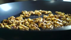 Roasting and mixing walnuts for dessert, slow motion video Stock Footage