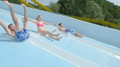 SLOW MOTION: Excited friends sliding down the water slide screaming Stock Footage