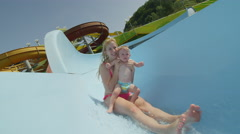 SLOW MOTION: Happy woman sliding on waterslide with baby boy Stock Footage