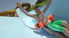 SLOW MOTION: Father and kid sliding down the water slide Stock Footage