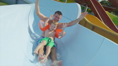 SLOW MOTION: Happy father and son sliding the waterslide toboggan - stock footage