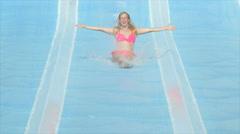 SLOW MOTION: Happy woman sliding down the fast waterslide toboggan - stock footage