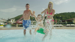 SLOW MOTION: Parents swinging their son, splashing water in waterpark - stock footage