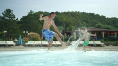 SLOW MOTION: Happy kid chasing his father in shallow pool - stock footage
