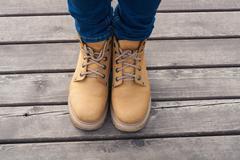 Boot on a wooden background. demi-season footwear. feet in footwear Stock Photos