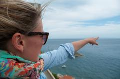 Young blond woman pointing with finger towards the ocean horizon - stock photo