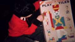 1961: Boy play tiles of Babes in Toyland educational building blocks. GREELEY, - stock footage