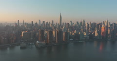 Manhattan as the sun sets helicopter shot from the East River Stock Footage