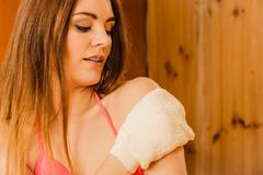 Stock Photo of Woman in sauna with exfoliating glove. Skincare.