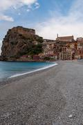 Stone beach and old small italian town on cliff under blue sky Stock Photos