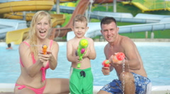 SLOW MOTION: Happy young family having a fun water fight Stock Footage