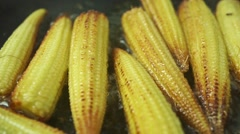 Roasting small corn cobs, macro dolly shot - stock footage