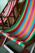 Colorful deck chair in front of a wooden door at hostel Stock Photos