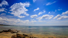 Stones in Transparent Shallow Azure Sea Blue Sky White Clouds Stock Footage