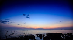 Pink Clouds in Dark Sky at Sunset over Sea Stones Silhouettes - stock footage