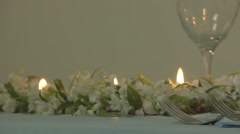 Tracking Shot of Floral Display, Lit Candles, and Dinnerware on Table - stock footage