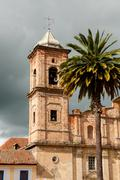 Old colonial stone church tower with palm tree near Bogota Stock Photos