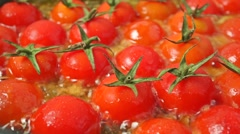 Frying ripe red cherry tomatoes. Close up dolly shot - stock footage
