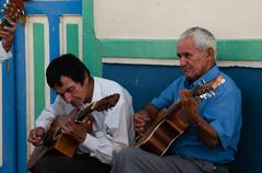 Closeup of two old man playing guitar on the street making music Stock Photos