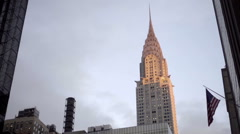 Famous Chrysler Building skyscraper and American flag tilting down Grand Central Stock Footage