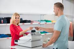 Stock Photo of Beautiful saleswoman receiving payment from male customer in store