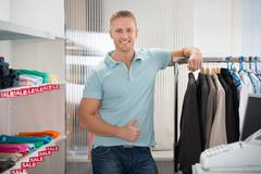 Portrait of confident salesman leaning on rack in clothing store Stock Photos